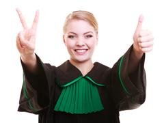 woman lawyer attorney in polish gown showing thumb up victory success hand sign - stock photo