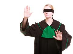lawyer attorney in classic polish gown covering eyes with blindfold - stock photo
