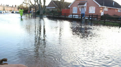 Waterwork official & cyclist in flood waters (tilt sandbag) Stock Footage