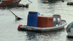 A small row boat with plastic containers berthing at sea. Stock Footage