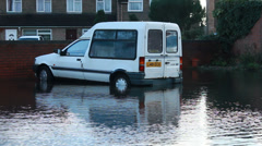 UK floods 2014, car drives out of flooded carpark Stock Footage