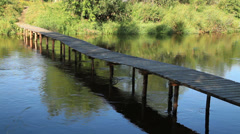Wooden bridge across the river Stock Footage