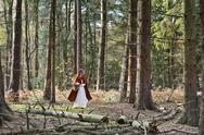 Stock Photo of Girl masquerade as Red Riding Hood on the move in the wood