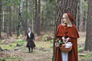 Stock Photo of Girl masquerade as Red Riding Hood hiding behind a tree in the wood