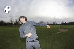 Young man heading a football - stock photo