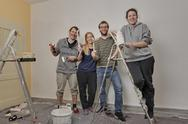 Stock Photo of Group picture of four friends renovating apartment together