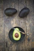 Two whole and a half avocado (Persea Americana) on wooden table - stock photo