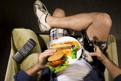 A man eats junk food Stock Photos