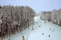 winter snowy forest and a chairlift for skiers - stock photo