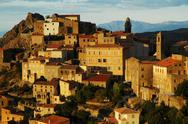 Stock Photo of Speloncato village on a rocky height in Corsica, in late afternoon lights