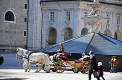 horse driven carriage with tourists in Salzburg - stock photo