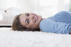 Stock Photo of Portrait of smiling woman lying on a carpet