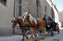 Salzburg – march 13: horse driven carriage with tourists near the franciscan Stock Photos