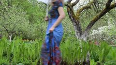 Woman dress welly shoes walk fern blooming fruit trees garden Stock Footage