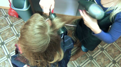 Closeup of stylist hands dry client woman hair with hairdryer Stock Footage