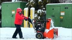 Man pushes snowblower, clears sidewalk Stock Footage