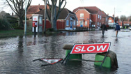 Stock Video Footage of Flood sign & Slow sign in flooded street, residents in background