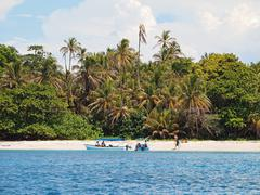 Boat tour with tourists on a tropical beach Stock Photos