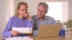 Old couple trying to figure out finances Stock Footage