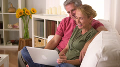Mature couple using laptop on couch - stock footage