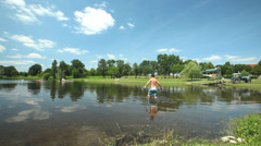 Child swimming in water on June 26, 2013 on Tauriac lake, France. Stock Footage
