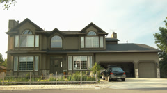 Curbside View Of A Suburban Home With A Fenced Yard And Car In The Driveway Stock Footage
