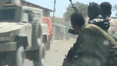 armed somali soldiers in truck wait for MRAP to pass - stock footage