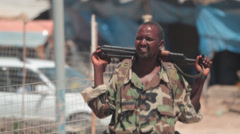 Somali soldier relaxing with AK-47 Stock Footage
