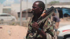 Somali soldier standing with AK-47 over shoulder Stock Footage
