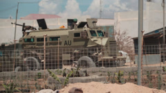 Ugandan soldier ready with machine gun on top of MRAP Stock Footage