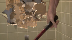 Hammer pounds away tile in shower stall. - stock footage
