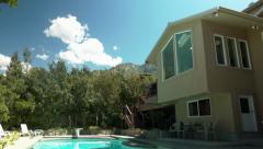 Pan From Blue Sky to A Beautiful Suburban Home And Gorgeous Pool Stock Footage