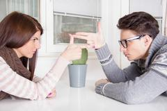 Couple in confrontation pointing at each other with challenge attitude Stock Photos