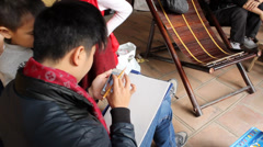 Artist painting portrait for visitor at folk festivals Stock Footage