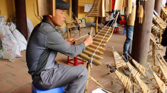 Asian man playing traditional instruments made of bamboo at folk festival Stock Footage