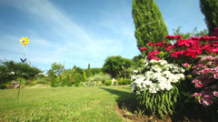 Tracking of flower bed in front of wooden house Stock Footage