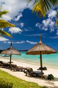 Mauritius beach, parasols, palms, green water, postcard motive - stock photo