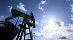 Oil rig pumping over sky. - stock footage