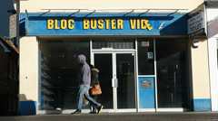 Pedestrians pass bankrupt Blockbuster video store (wide) Stock Footage