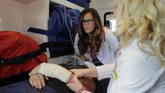 Medical team transporting an injured patient in ambulance after the accident. Stock Footage