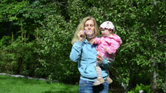 Woman with daughter spend time in park blowing big soap bubbles Stock Footage