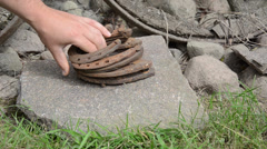 Hand put stack of retro rusty horse shoes on big stone Stock Footage