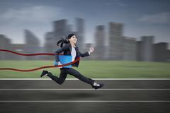 Businesswoman winning on a race Stock Illustration