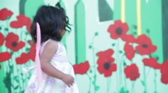Toddler run in front of the stage, suddenly she goes went and turns back Stock Footage