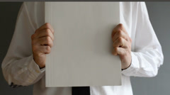 Businessman holding blank paper with copy space for business message - stock footage