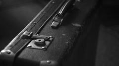 Vintage suitcase stands on the floor, black and white Stock Footage