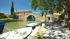 Boats and bridge on June 22, 2013 in Le Somail on the Canal du Midi, France. Stock Footage