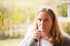 Woman has a cold, nasal spray taking Stock Photos