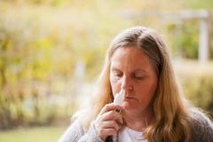 woman has a cold, nasal spray taking - stock photo
