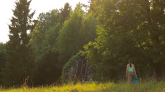Girl walking to the forest in the country, sun rays Stock Footage